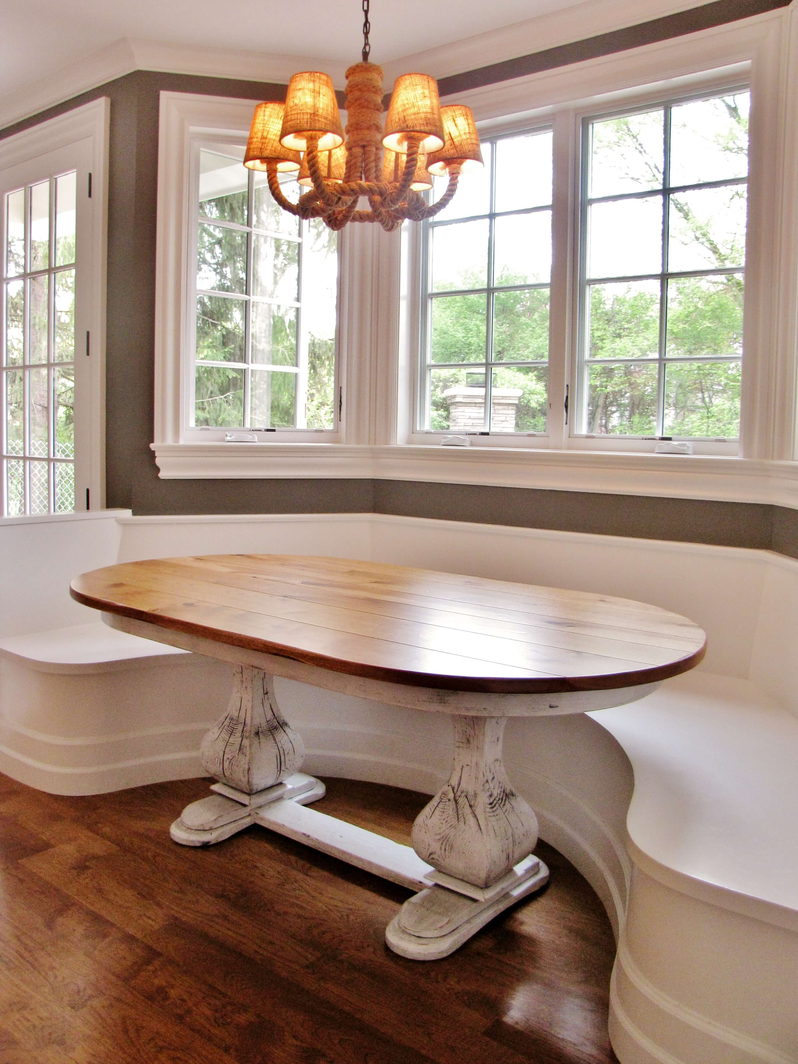 Whitewashed oval tables with a built-in bench.